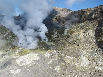 White Island showing a wide view of the active crater area. The lava dome is at the base of the prominent steam plume on the right side. The larger steam plume on the left side comes from a hot lake.