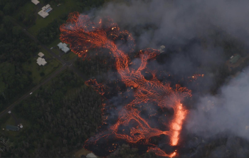 A lava flow released by one of the recent fissures in Leilani Estates in the Puna District of Hawaii threatens roads, houses, and infrastructure. (Photo by Ann Kalber of Tropical Visions Videos).