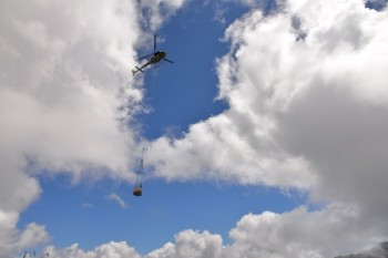 Helicopter carrying the temporary monitoring station into place